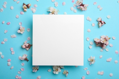 Flat lay composition with fresh spring flowers and blank card on color background, space for text