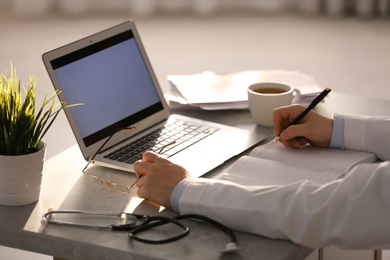 Professional doctor with laptop working in office, closeup