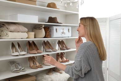 Young woman near shelving unit with shoes and accessories in dressing room
