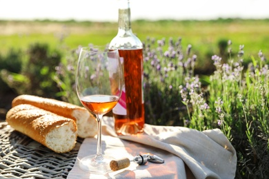 Composition with glass of wine on wicker table in lavender field