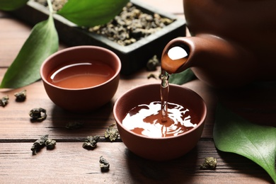 Pouring Tie Guan Yin oolong tea into cup on wooden table