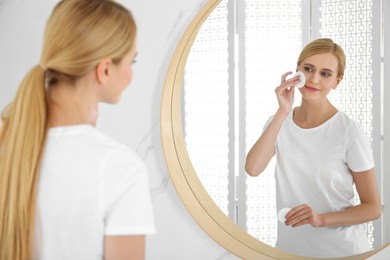 Happy young woman cleaning face with cotton pad near mirror in bathroom