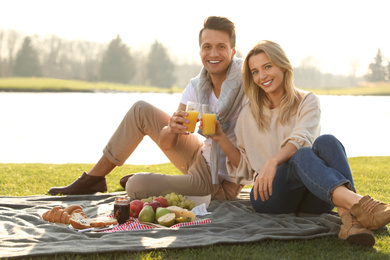 Happy young couple having picnic near lake on sunny day