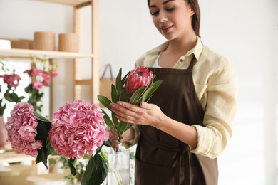 Florist with beautiful protea flower in workshop