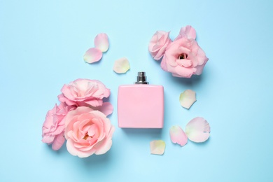 Flat lay composition with bottle of perfume and flowers on light blue background