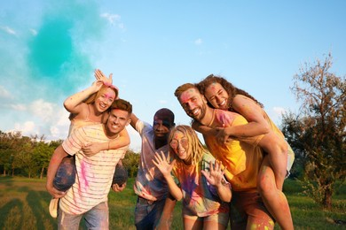 Happy friends covered with colorful powder dyes outdoors. Holi festival celebration