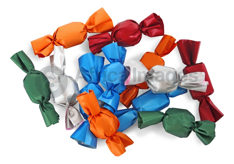Many candies in colorful wrappers on white background, top view