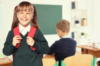 Happy girl with backpack in school classroom