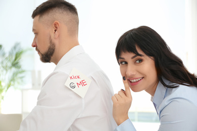 Young woman sticking KICK ME note to colleague's back in office. April fool's day