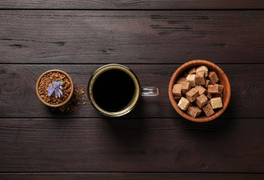 Glass cup of delicious chicory drink, granules, brown sugar and flower on wooden table, flat lay