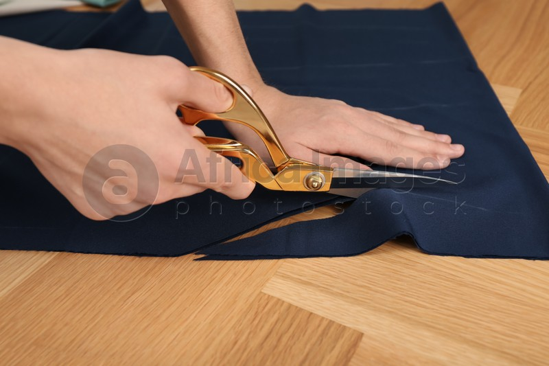 Man cutting blue fabric with scissors at wooden table, closeup