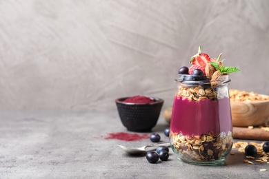 Delicious acai dessert with granola and berries served on grey table. Space for text