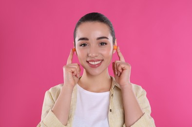 Young woman inserting foam ear plugs on pink background