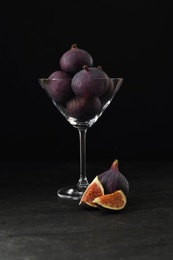 Tasty raw figs in martini glass on black table