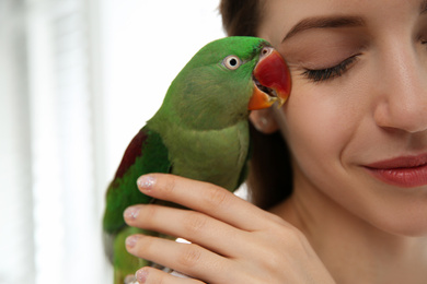 Young woman with cute Alexandrine parakeet on light background, closeup