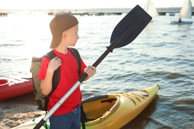 Little boy with paddle near kayak on river shore. Summer camp activity