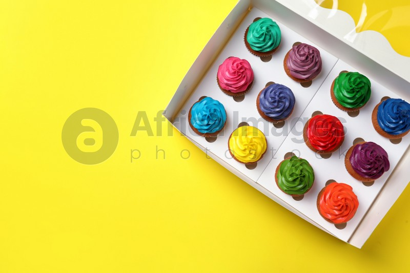 Box with different cupcakes on yellow background, top view. Space for text