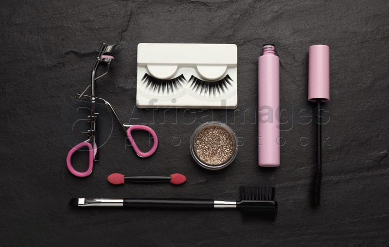 Flat lay composition with eyelash curler, makeup products and accessories on black table