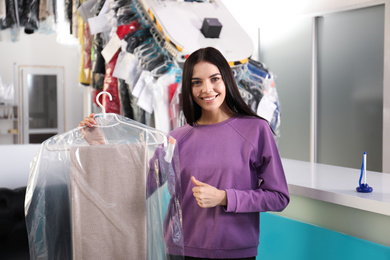 Happy client with clothes near counter at dry-cleaner's