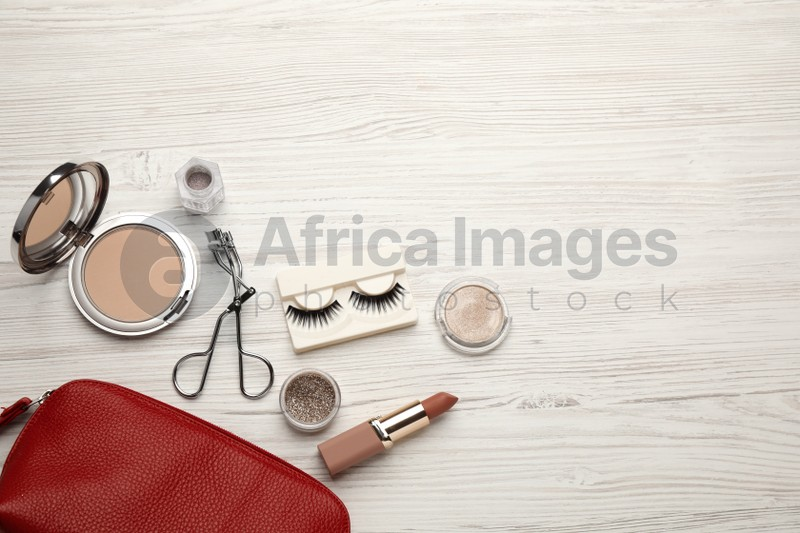 Flat lay composition with eyelash curler, makeup products and accessories on white wooden table. Space for text