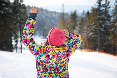 Young woman at mountain resort, back view. Winter vacation