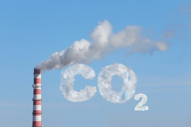 Inscription CO2 made of smoke. Polluting air from industrial chimney outdoors against blue sky