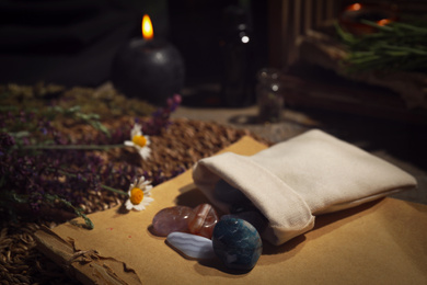 Bag with gemstones and healing herbs on table