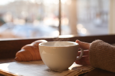 Woman with cup of delicious morning coffee near window indoors
