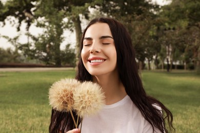 Beautiful young woman with large dandelions in park. Allergy free concept