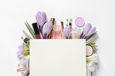 Makeup products, spring flowers and blank card on white background, top view. Space for text