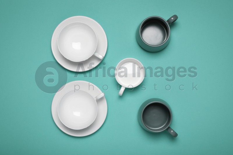 Different cups on turquoise background, flat lay
