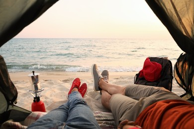 Couple resting in camping tent near sea, closeup