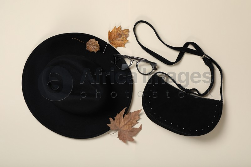 Stylish hat, bag and autumn leaves on beige background, flat lay