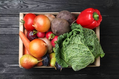 Crate full of different vegetables and fruits on black wooden table, top view. Harvesting time