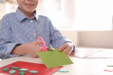Little girl making greeting card at table indoors, closeup with space for text. Creative hobby