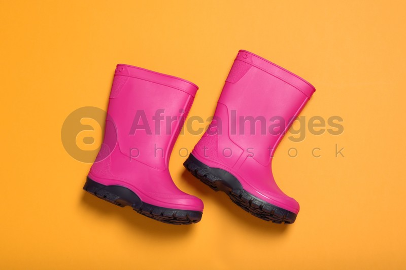 Pair of bright pink rubber boots on orange background, top view