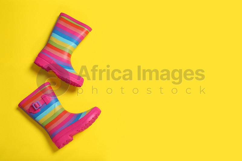 Striped rubber boots on yellow background, top view. Space for text