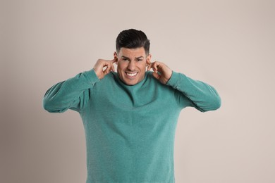 Emotional man covering ears with fingers on beige background