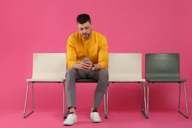 Man with smartphone waiting for job interview on pink background