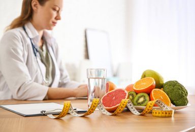 Healthy products, measuring tape and blurred nutritionist on background