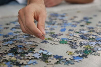 Man playing with puzzles on floor, closeup