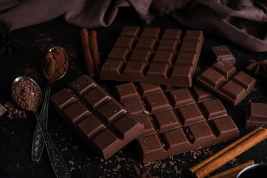 Tasty milk chocolate and spoons with cocoa powder on black table