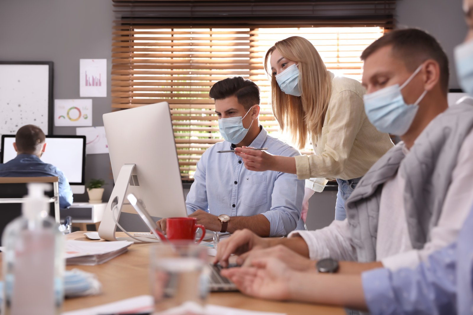 Coworkers with masks in office. Protective measure during COVID-19 pandemic