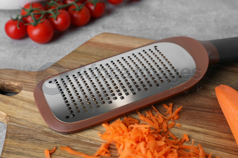 Hand grater and fresh ripe carrot on wooden board, closeup
