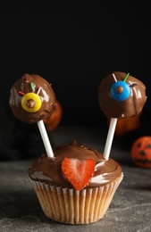 Delicious desserts decorated as monsters on grey table. Halloween treat