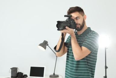 Young man with professional camera in photo studio