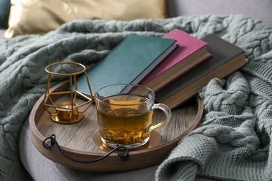 Stylish tray with different interior elements and tea on sofa