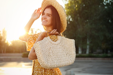 Young woman with stylish straw bag outdoors