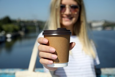 Woman holding takeaway cardboard coffee cup with plastic lid outdoors, closeup