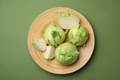 Whole and cut kohlrabi plants on green background, top view